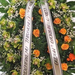 Wieniec pogrzebowy stojący z żywych herbacianych róż i storczyków